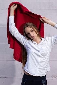Belle femme blonde aux cheveux longs porte une chemise blanche posant sur un mur blanc dans la rue