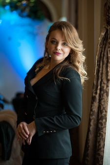 Belle femme blonde aux cheveux ondulés dans un costume noir d'affaires