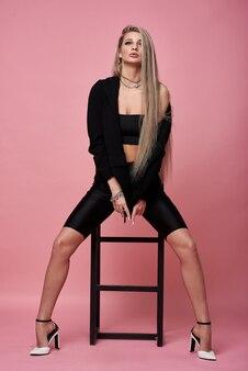 Belle femme blonde aux longues jambes dans une veste noire pose sur une grande chaise sur fond rose