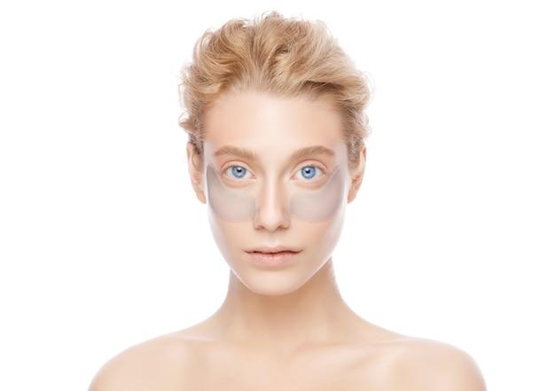 Belle femme blonde aux yeux bleus avec une peau éclatante avec des patchs pour éliminer les poches des yeux