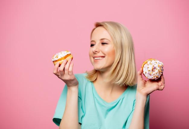 Belle femme blonde avec beignet sur mur rose