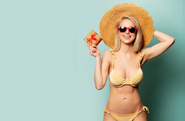 Belle femme blonde en bikini avec une boîte cadeau