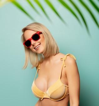 Belle femme blonde en bikini avec une branche de palmier