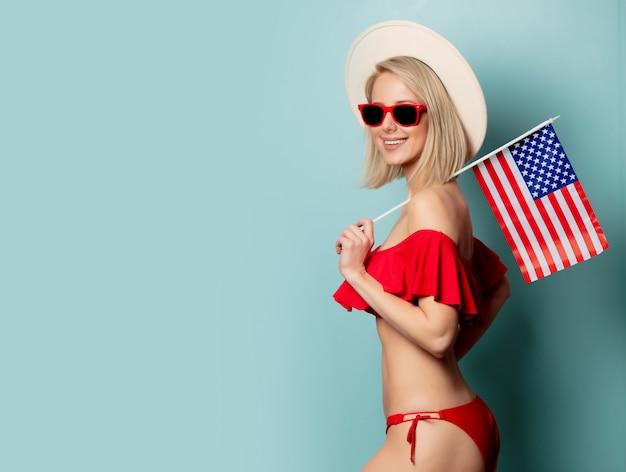 Belle femme blonde en bikini avec drapeau usa