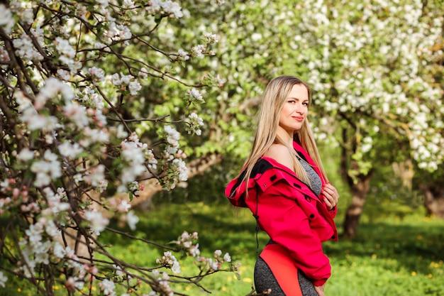 Belle femme blonde en blouson d'encre à l'extérieur au printemps. jardin fleuri.