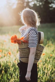 Belle femme blonde avec un bouquet de coquelicots et un chapeau de lin dans un champ d'été par une journée ensoleillée.