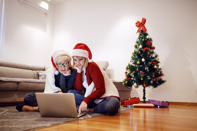 Belle femme blonde caucasienne assise avec sa mère sur le sol dans le salon et à l'aide d'un ordinateur portable. les deux ont des chapeaux de père noël sur la tête. en arrière-plan est décoré de sapin de noël.