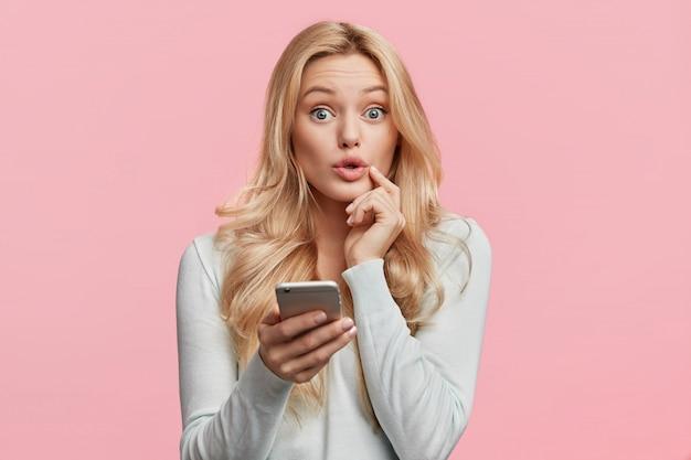 Belle femme blonde avec une chemise blanche tenant le téléphone