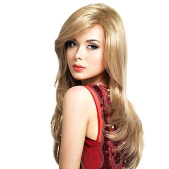 Belle femme blonde avec une coiffure longue pose au studio