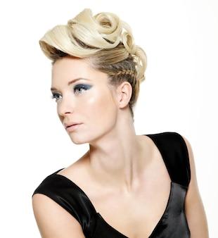 Belle femme blonde avec une coiffure moderne et un maquillage bleu des yeux isolé sur blanc