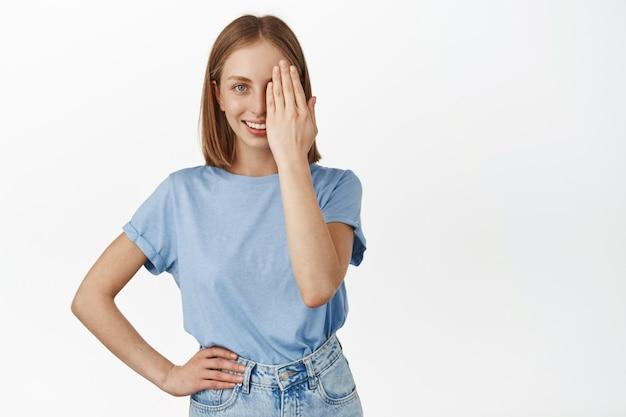 Belle femme blonde couvre la moitié du visage, regardant d'un œil et souriant confiant, avant et après l'effet, debout en t-shirt bleu contre un mur blanc