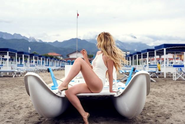Belle femme blonde dans un bateau à la plage de forte dei marmi, italie