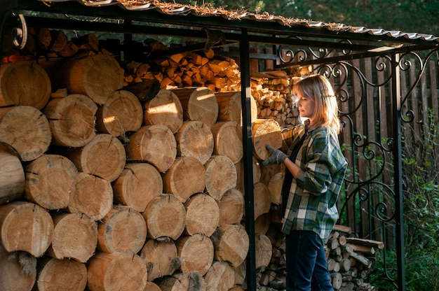 Une belle femme blonde dans une chemise à carreaux recueille le bois d'un poêle à bois la vie rurale quotidienne