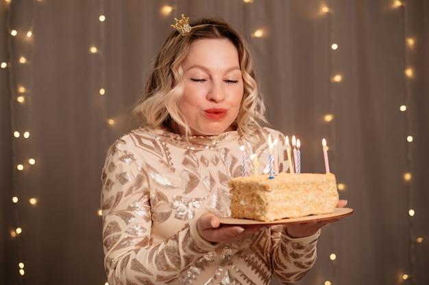 Belle femme blonde dans une petite couronne sur sa tête avec un gâteau d'anniversaire et des bougies.