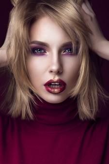 Belle femme blonde dans un pull rouge avec un maquillage lumineux et des lèvres sombres.