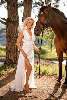 Belle femme blonde dans une robe blanche dans les bois avec un cheval sur une journée d'été ensoleillée