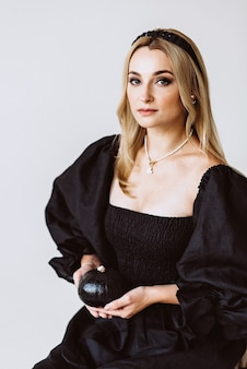 Belle femme blonde dans une robe en lin noir avec une citrouille dans ses mains. mode ethnique, tissu naturel. fête d'halloween. mise au point sélective douce.