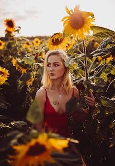 Belle femme blonde dans une robe rouge dans le domaine des tournesols