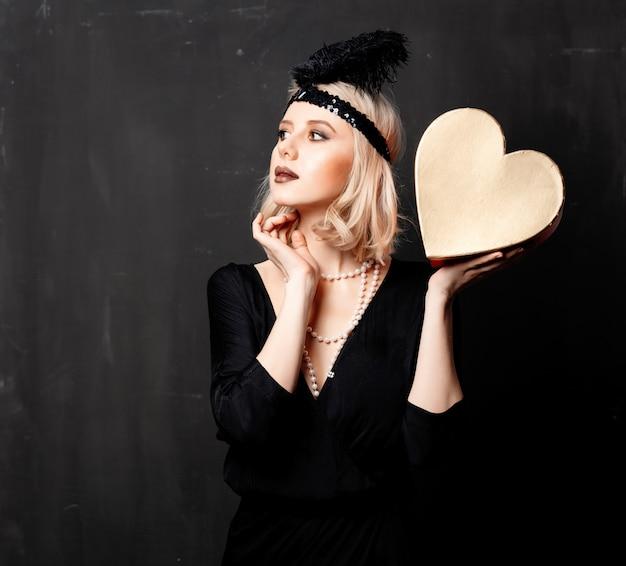 Belle femme blonde dans des vêtements des années vingt avec cadeau de saint valentin