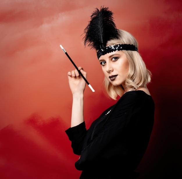 Belle femme blonde dans les vêtements des années vingt avec pipe à fumer sur fond rouge