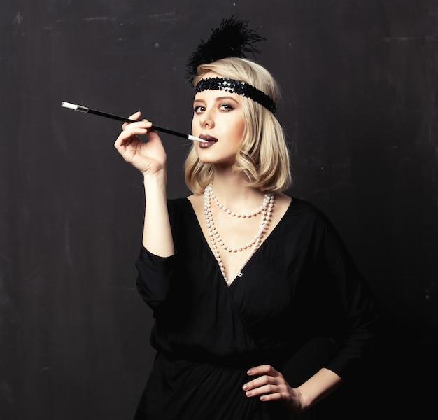 Belle femme blonde dans les vêtements des années vingt avec pipe à fumer sur fond sombre