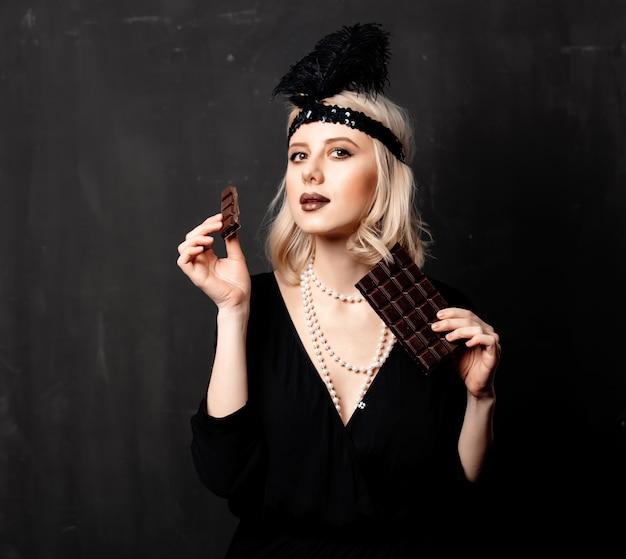 Belle femme blonde dans des vêtements années vingt avec une tranche de chocolat