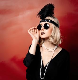 Belle femme blonde dans des vêtements et des lunettes de soleil années vingt