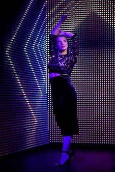 Belle femme blonde dans les vêtements à la mode, profiter de la vie nocturne, fille magnifique à l'intérieur sur l'illumination au néon.