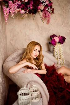 Belle femme blonde élégante sur le canapé en robe bordeaux