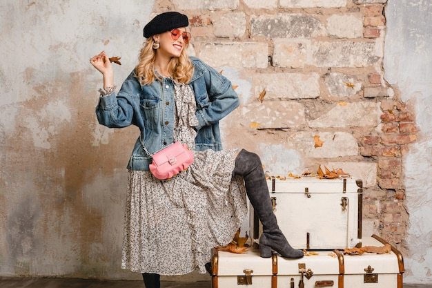 Belle femme blonde élégante en jeans et veste surdimensionnée posant contre le mur dans la rue