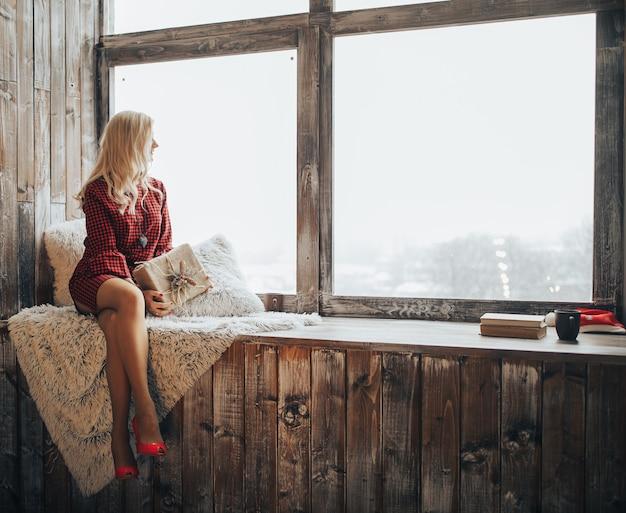 Belle femme blonde est titulaire d'une boîte-cadeau sur sa main regarde par la fenêtre