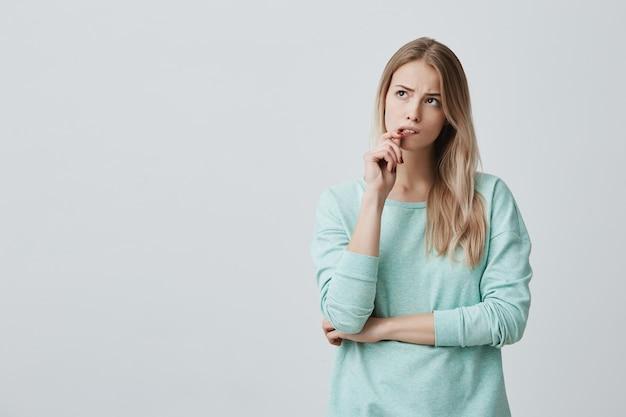 Belle femme blonde avec une expression perplexe, garde le doigt sur les lèvres, regarde de côté avec perplexité