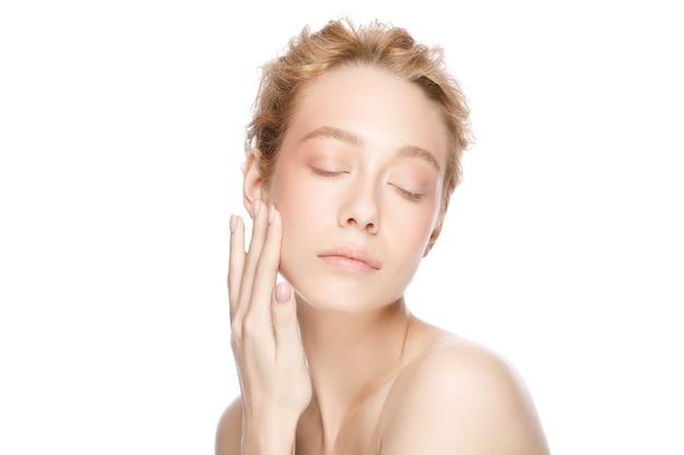 Belle femme blonde face aux yeux fermés touchant sa peau parfaitement propre avec la main