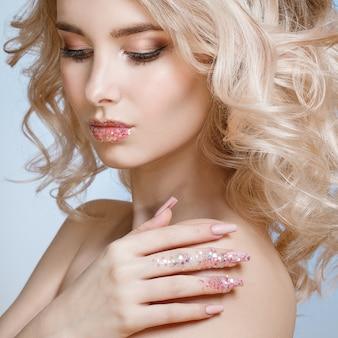 Belle femme blonde frisée avec un maquillage parfait, design ongle givré à la mode avec des paillettes.