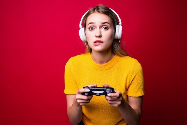 Belle femme blonde avec joystick et écouteurs sur mur rouge