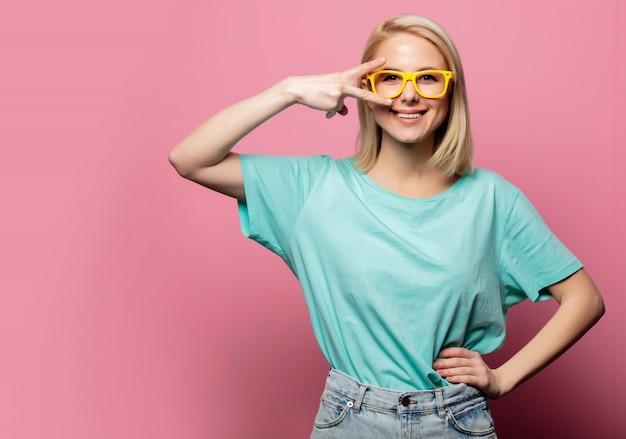 Belle femme blonde à lunettes jaunes sur mur rose