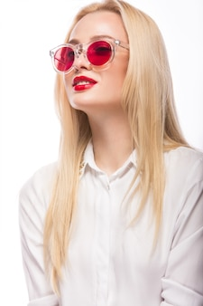Belle femme blonde à lunettes roses et chemise
