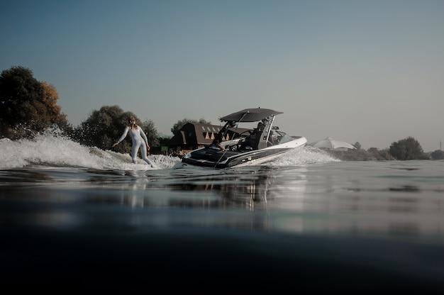 Belle femme blonde en maillot de bain blanc à cheval sur le wakeboard tenant une corde du bateau à moteur