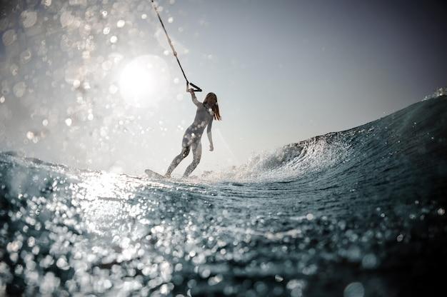 Belle femme blonde en maillot de bain blanc debout sur le wakeboard tenant une corde sur les genoux pliés