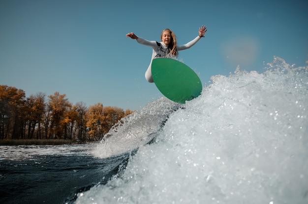 Belle femme blonde en maillot de bain blanc sautant sur le wakeboard vert sur les genoux pliés