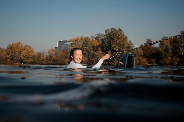Belle femme blonde en maillot de bain blanc tenant un wakeboard vert dans l'eau de la rivière