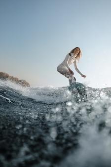 Belle femme blonde en maillot de bain sport blanc à cheval sur le wakeboard sur les genoux pliés