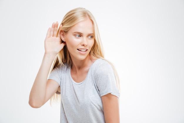 Belle femme blonde avec la main à l'oreille pour mieux entendre isolée sur un mur blanc