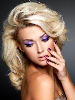 Belle femme blonde avec manucure pourpre beauté et maquillage des yeux