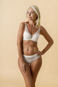 Belle femme blonde mature avec un corps en forme en sous-vêtements blancs souriant à la caméra tout en posant