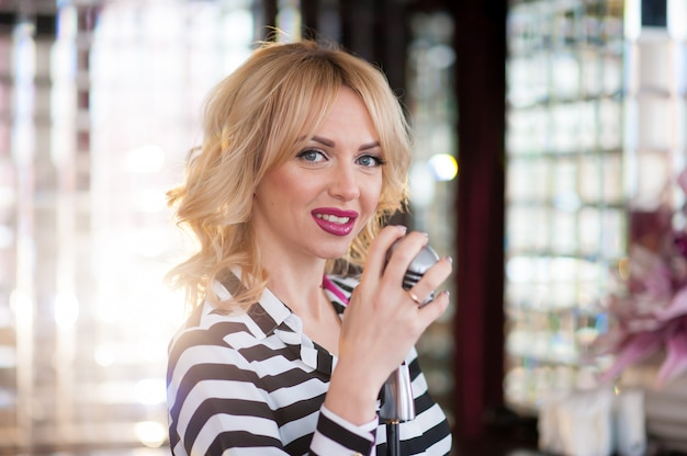 Belle femme, blonde, microphone. chant, beau sourire