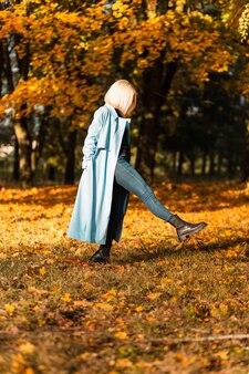 Belle femme blonde à la mode dans un manteau bleu et un jean se promène dans un parc d'automne au feuillage jaune