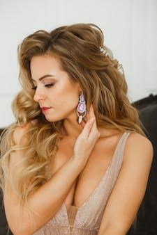 Belle femme blonde montrant sa coiffure grecque parfaite et ses boucles d'oreilles en cristal de couleur violette avec des perles. en beige posant en studio