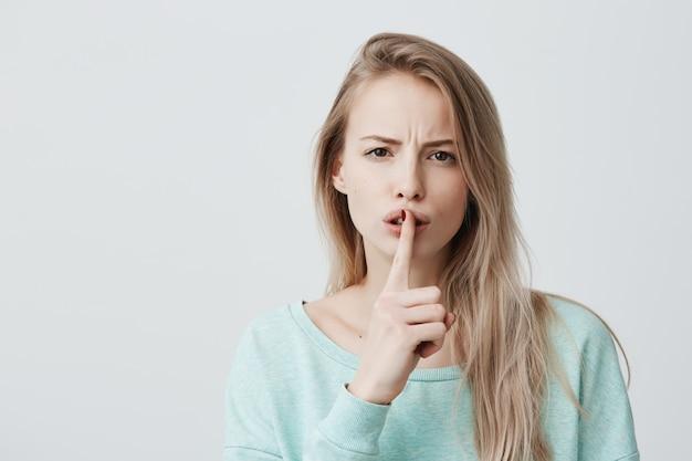 Belle femme blonde montre un signe de silence, a une expression sérieuse, demande le silence.
