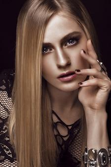 Belle femme blonde avec une peau et des cheveux sains, manucure rouge, qui pose en studio